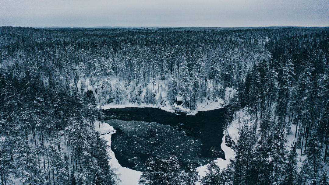 Beautiful Oulanka river in winter. The ice is spinning around in vortex in this place.